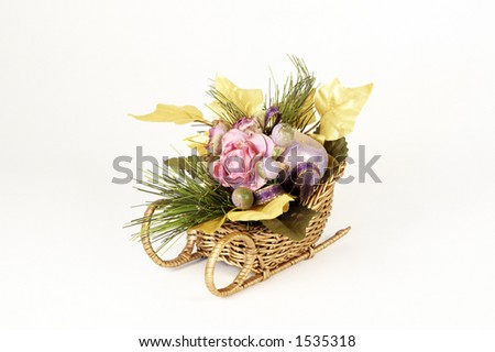 Artificial flowers in a sleigh on white background. - stock photo