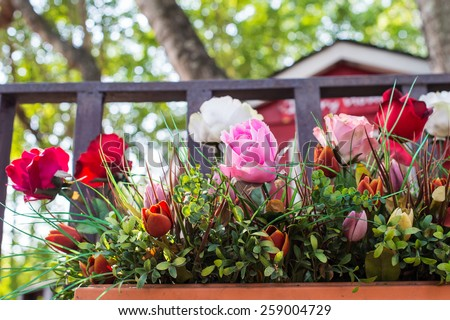 Artificial flowers in the basket in vintage theme - stock photo
