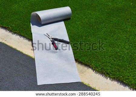 Artificial grass turf installation in garden with tools and joint roll - stock photo