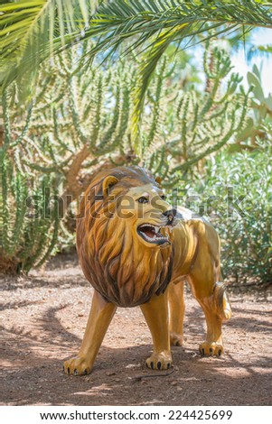 Artificial lion in national park. Toy for kids. - stock photo