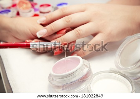Artificial nails in a beauty salon. Hands close-up. The process of nails. - stock photo