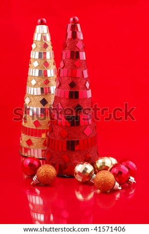 Artificial red and yellow christmas trees and glass balls on red background - stock photo