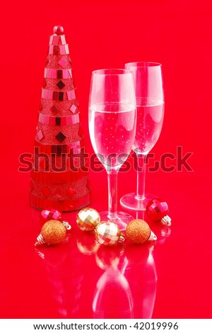 Artificial red christmas tree and champagne on red background - stock photo