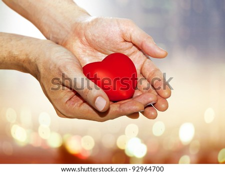 artificial red heart on hands of man - stock photo