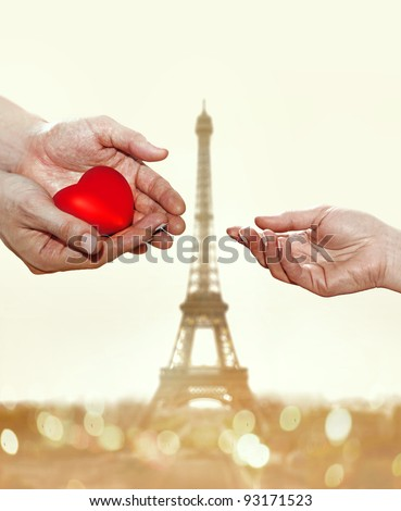 artificial red heart on hands of man for woman on Eiffel Tower background