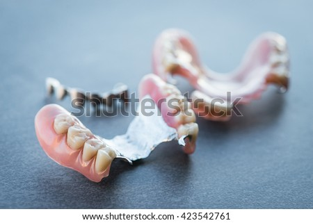 Artificial replacement teeth on a dark surface - stock photo