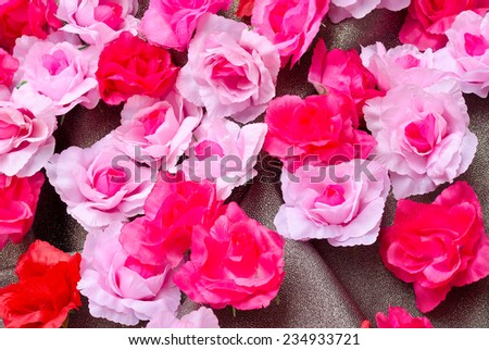 Artificial rose flower on glitter texture - stock photo