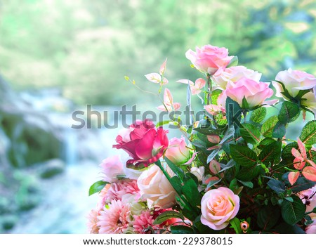 artificial roses flowers bouquet arrangement against green blur background - stock photo