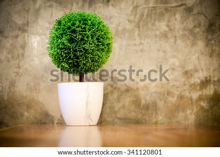 artificial small tree in a white flower pot with retro cement wall. - stock photo