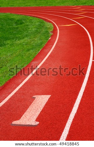 Artificial surface 400m athletic track with clean fresh markings - stock photo