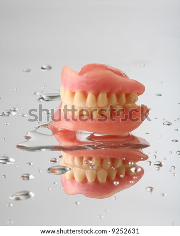 artificial teeth on reflecting background, with water drops