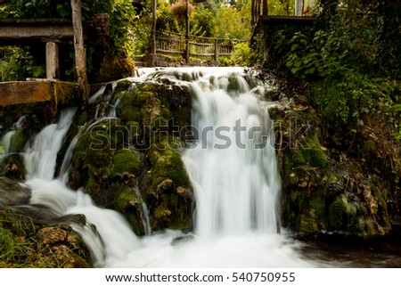 Artificial waterfall with a long exposure in the village of Slunj in Croatia in parts of Rastoke . White water streams in the greens on the background of old wooden planks. A small waterfall drips
