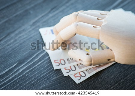 Artificial wooden hand holding the money, on a rustic wooden table - stock photo