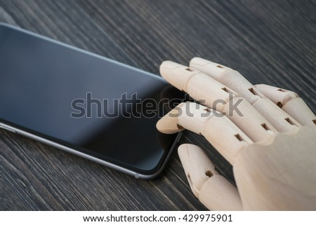Artificial wooden hand with modern phone on wooden table