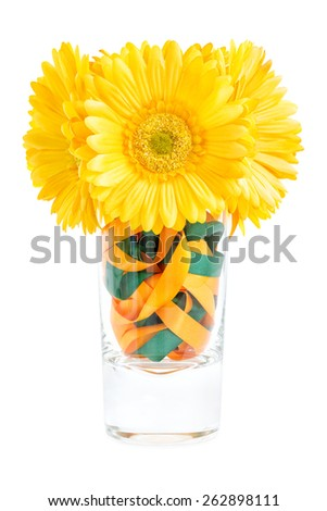 Artificial yellow Gerbera flower bouquet in a crystal vase with satin ribbons, isolated on white - stock photo