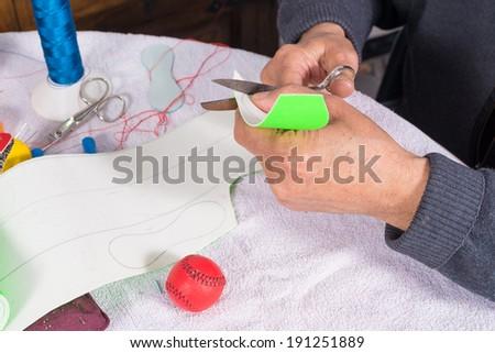 Artisan cutting out stripes of leather to make traditional  jai alai balls - stock photo