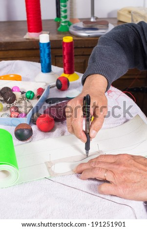 Artisan drawing a pattern to cut out  a piece of leather - stock photo