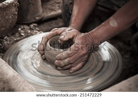Artisan hands making clay pot - stock photo