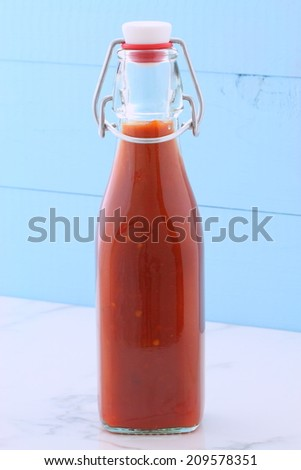 Artisan mexican red hot sauce on retro vintage carrara marble in antique bottle, perfect for all your Mexican, tex-mex recipes and sides. - stock photo