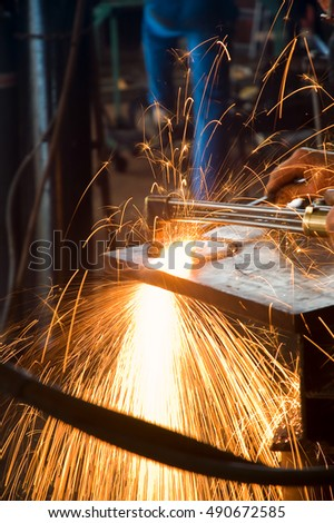 Artisan using Gas Cutting Torch to Cut Through Thick Metal Plate.
