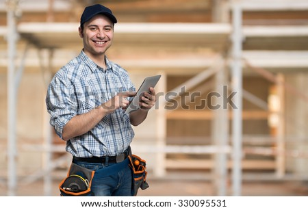 Artisan using his tablet computer in a construction site - stock photo