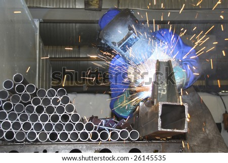 Artisan welding tubes in a production line - stock photo