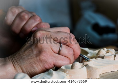 Artisan woodcarver creates a furniture ornament. Woodcarver's hands, chisels, tools, wood-carved ornament. - stock photo