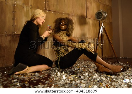 Artist applying makeup to beautiful african american model at photo shoot on floor in bright gold studio - stock photo