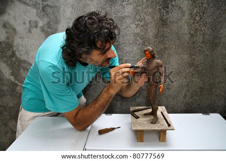 artist at work on a plasticine miniature of human body - stock photo