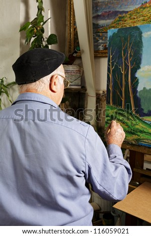 Artist at work painting picture in workshop rear view - stock photo