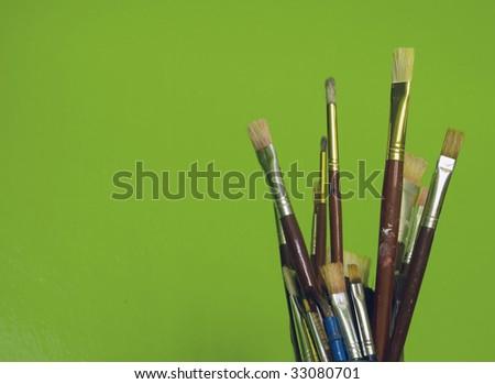 Artist brushes on green (2) - stock photo