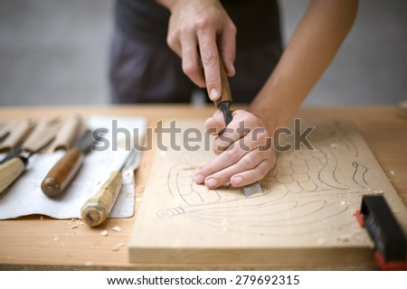 Artist carves a wooden plate with a chisel,shallow depth of field - stock photo