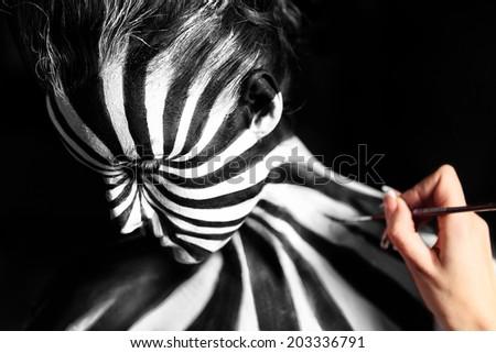 Artist create body art on the girl's body. Look like zebra pattern skin - stock photo