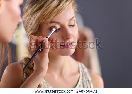 Artist doing professional make up of woman - stock photo