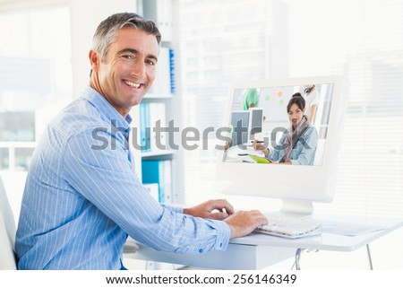 Artist drawing something on graphic tablet with colleagues behind against smiling man typing on keyboard and looking at camera - stock photo
