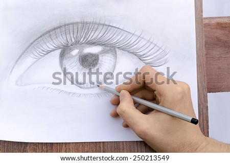 artist draws an eye a pencil - stock photo