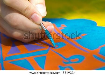 Artist fingers with brush, doing artwork - stock photo