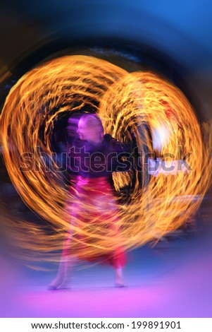 Artist juggling with two burning poi's at fire performance. Long exposure causing painting with light  - stock photo