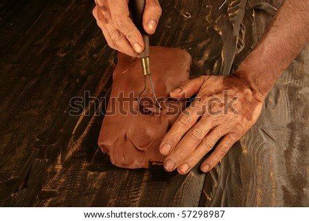 artist man hands working red clay to create handcraft art