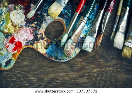 Artist paint brushes and palette on wooden background - stock photo
