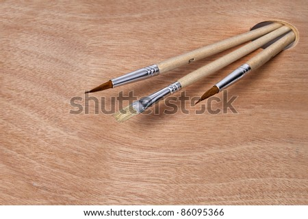 Artist paint brushes on clean wooden palette background