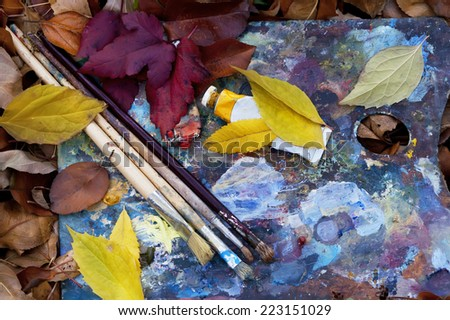 Artist paintbrushes over the artist palette in a heap of leaves, overhead shot - stock photo