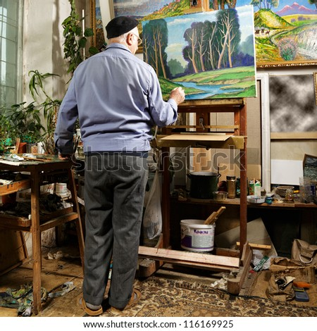 Artist painting picture in workshop rear view - stock photo