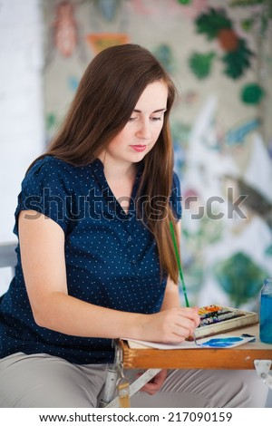 Artist painting picture on canvas with watercolors in her white studio - stock photo