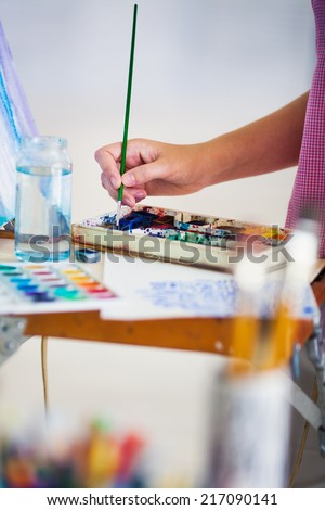 Artist painting picture on canvas with watercolours - stock photo