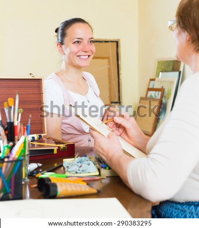 Artist  painting  portrait of girl at workshop - stock photo