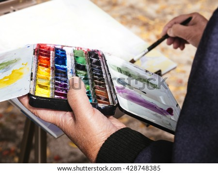 Artist painting water colors People Leisure lifestyle outdoor - stock photo