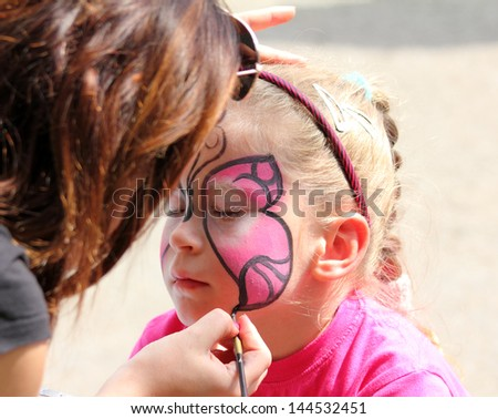 artist paints butterfly on face of cute little girl - stock photo