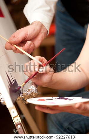 Artist paints with colors on a canvas - stock photo