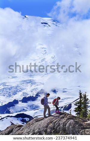 ARTIST POINT, WASHINGTON-JULY 26, 2014 Asian Hikers Hiking Near Mount Baker Snow Mountain Under Clouds from Artist Point  Mount Baker Highway Washington State Pacific Northwest - stock photo